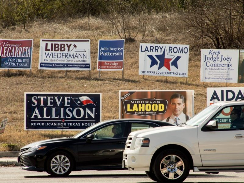 Campaign signs are posted along Hildebrand Avenue next to the entrance of U.S. Highway 281.