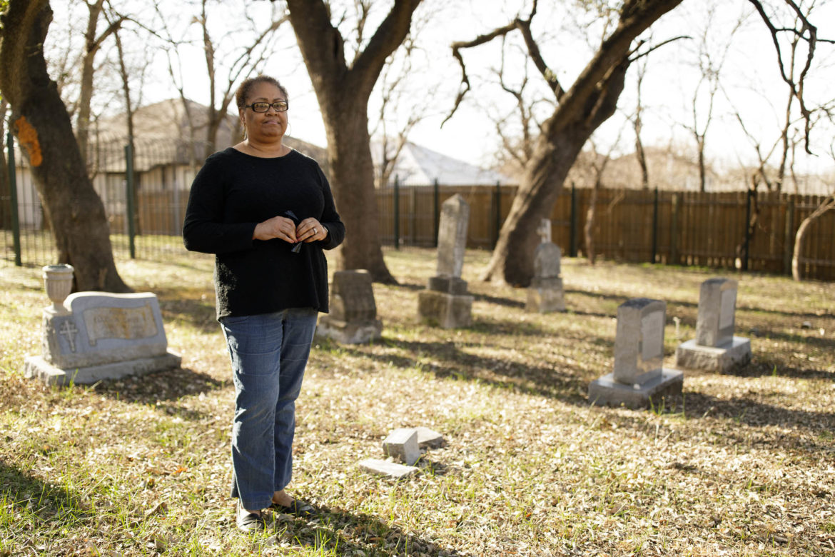 """Melanie Brooks stands in the cemetery of her relatives. """"We want to forget"""" she says in response to the lack of taught history of the African-American population."""