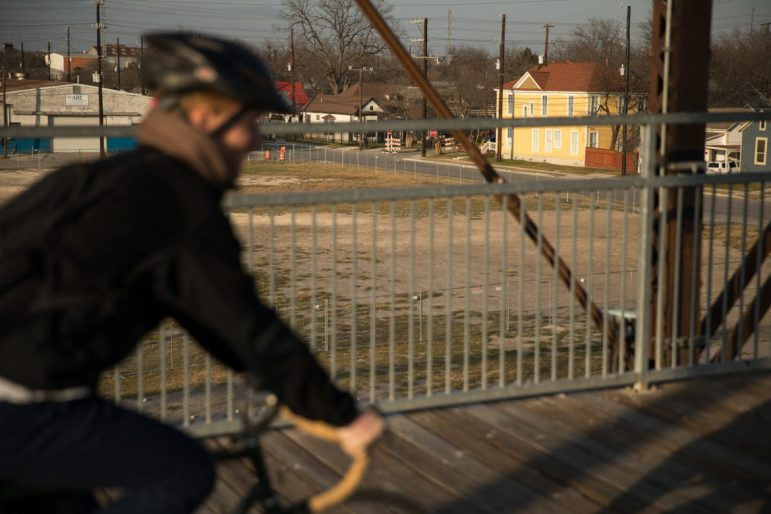 A cyclists rides East on Hays Bridge towards Dignowity Hill.