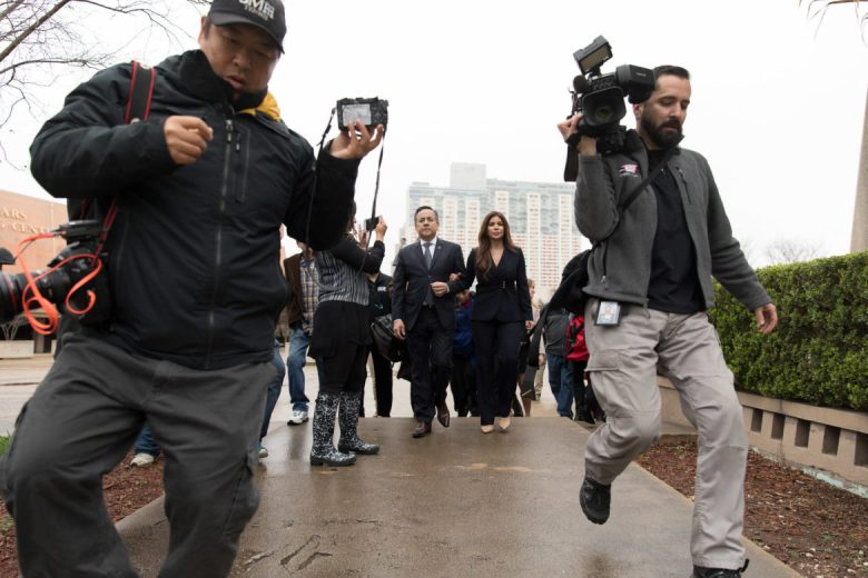 News reporters run in front of State Sen. Carlos Uresti and his wife Lleanna Uresti walk from the Federal Courthouse after receiving the verdict of 11 guilty charges.