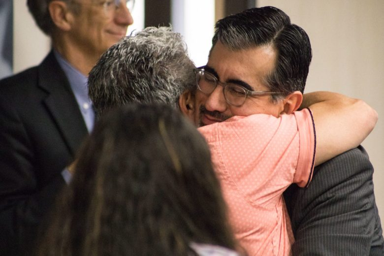 Mike Flores hugs friends and family before hearing that he will take over as Alamo Colleges chancellor on Oct. 1.