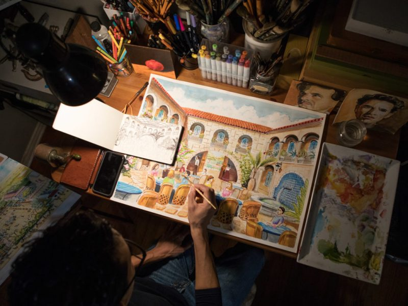 Artist Claudio Aguillon works on his paintings for Chef Johnny Hernandez in his home.
