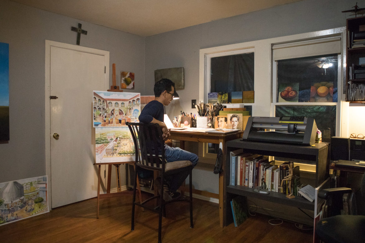Artist Claudio Aguillon works on his paintings in his home.