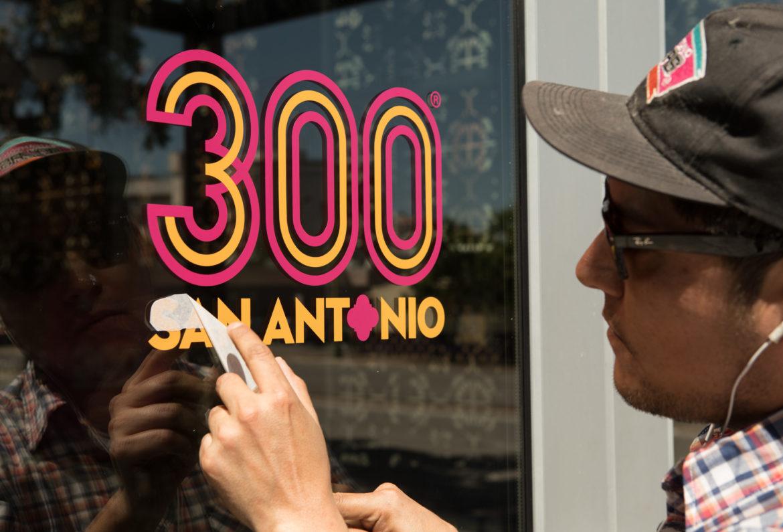 Rigoberto Luna installs the decals on the doors of the new Tricentennial merchandise shop at Centro de Artes.