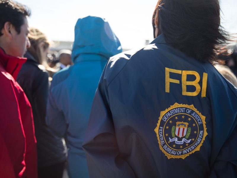 A member of the Federal Bureau of Investigation stands with other law enforcement members and reporters during the press conference.