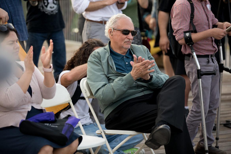Mario Salas applauds while attending the vigil.
