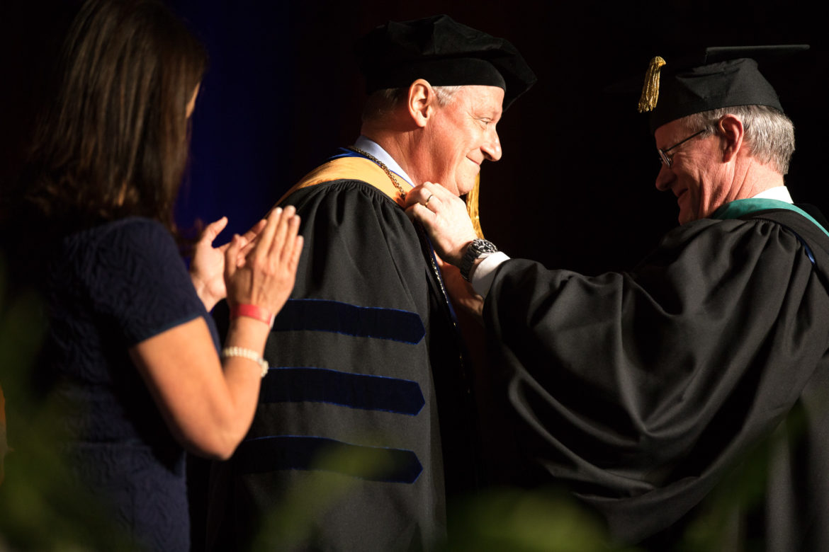 UTSA President Eighmy is given the President's medal by University of Texas System Chancellor William McRaven Eighmy's wife, Peggy applauds.