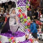 A queen of the court's gown is displayed on a float as she shows her shoes.