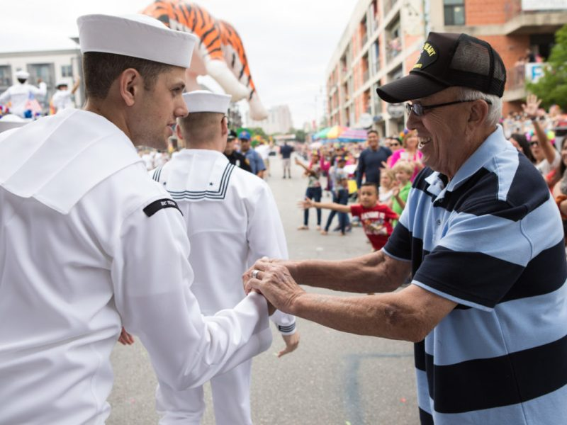 A man from the Navy Medicine Training Support Center thanks Fred Navarro (right) for his service in the military.