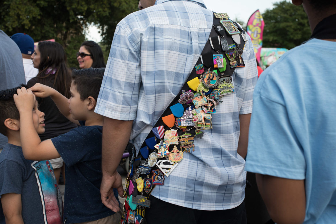 A man wears a sash with many fiesta medals during Fiesta Fiesta at Hemisfair.