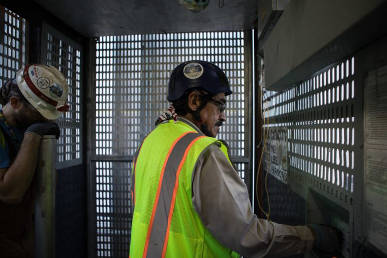 Sylvester Luna operates the freight elevator of the Frost Tower construction site.