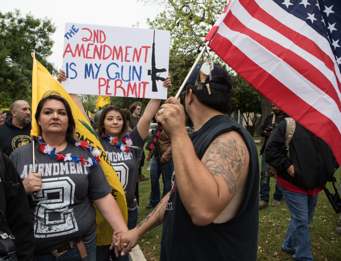 (From left) Maria Sanchez and James Sanchez march through Olmos Park and to the front door of its City Hall on Saturday to demand the resignation of Police Chief Rene Valenciano.
