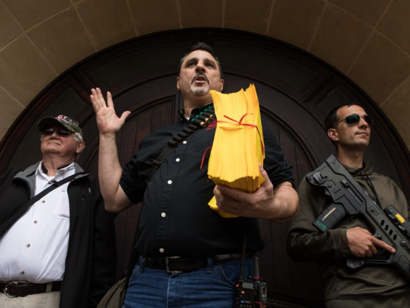 (From left) Rick Briscoe, legislative director of Open Carry Texas, David Amad, vice president of Open Carry Texas, and Colt Szczygiel hold petitions against government abuse of lawful gun owners in front of Olmos Park City Hall.
