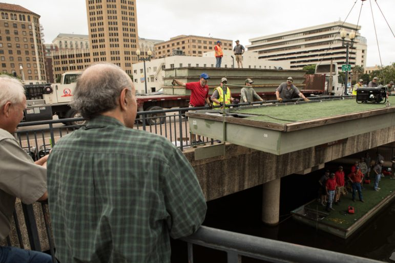 """The Texas Cavaliers lower a barge into the river on """"Barge-in"""" Day so they can be decorated for the upcoming Texas Cavaliers Fiesta River Parade."""