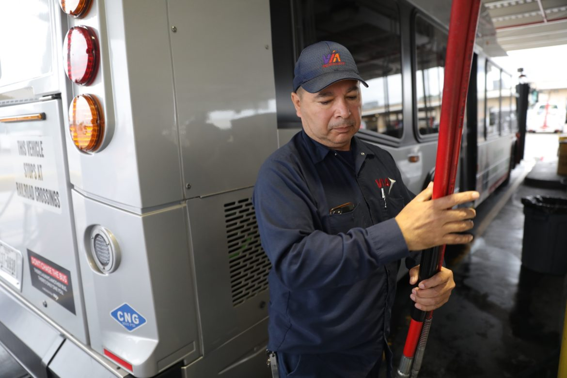 27 year VIA employee Gilbert Perez works to refuel a bus with compressed natural gas.