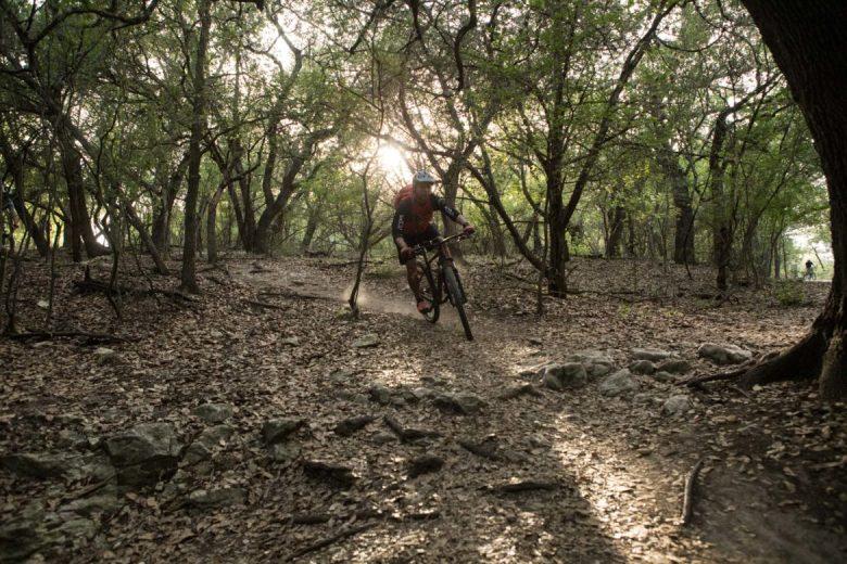 Erik Hernandez drops into the Leon Creek Greenway from OP Schnabel Park on his mountain bike.