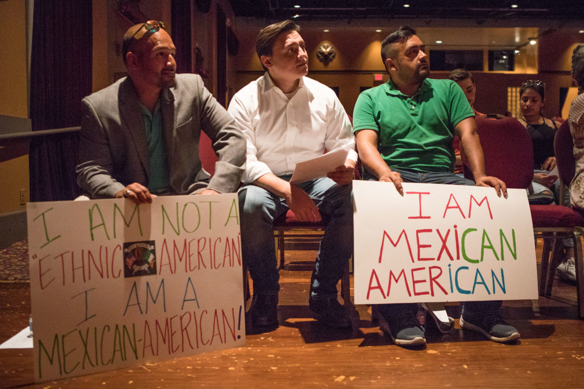 (From left) Victor Moreno, Rick Treviño, and Juan Moreno hold up signs in support of Mexican American Studies.