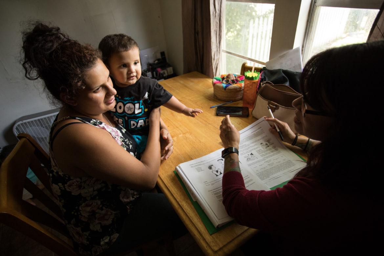 (From left) Monica Lara holds her son Jordan as she works with promotora Maranda Hernandez.