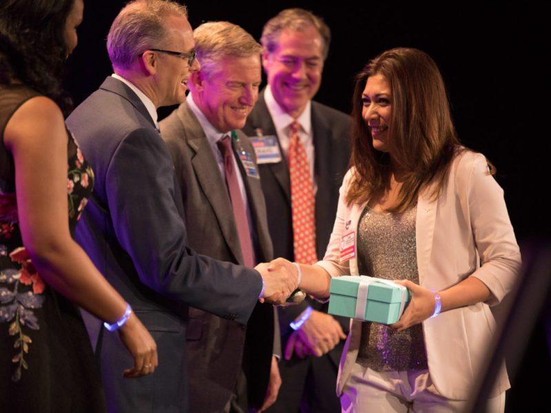 Christa McAuliffe Middle School teacher Denisse Hernandez is congratulated by H-E-B leadership.