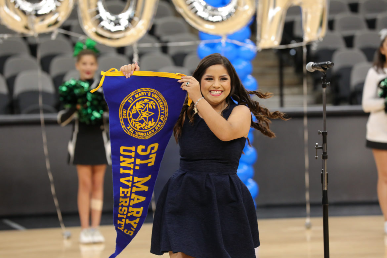 Senior Ainara Mora unveils a St. Mary's University flag to the cheering students.