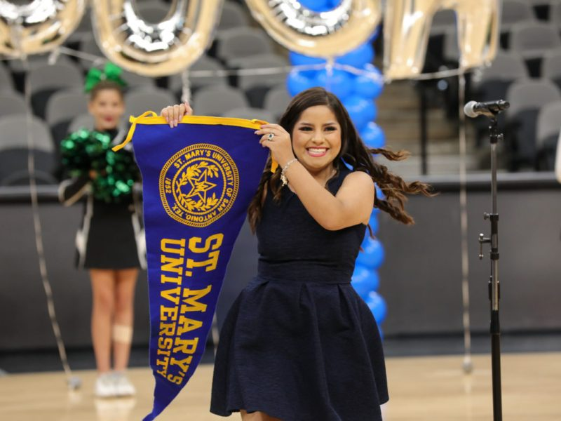 Senior Ainara Mora unveils a St. Mary's University flag to the cheering students.