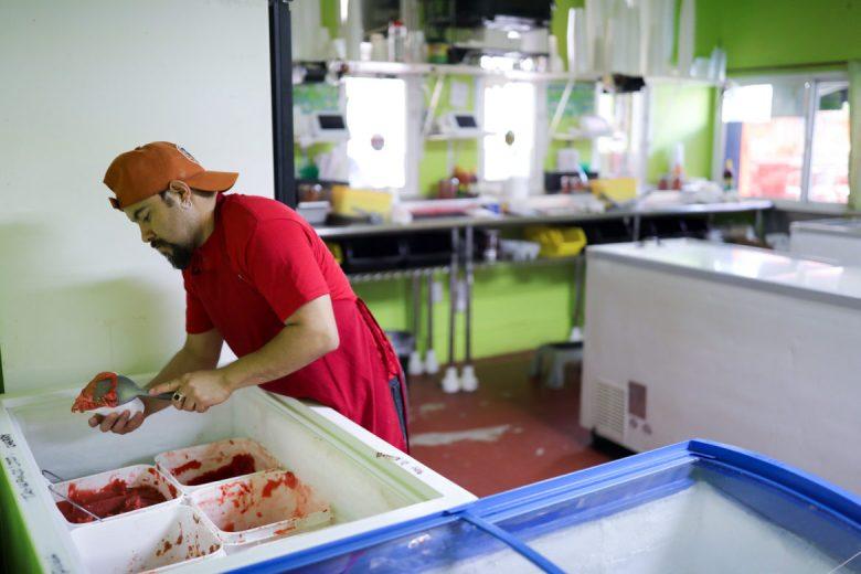 Las Nieves employee Marcelino Garfios scoops large chunks of Italian ice for customers.