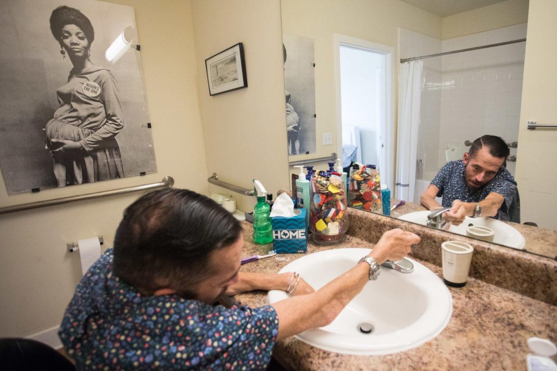 Adam Flores-Boffa washes his hands in his apartment's bathroom.