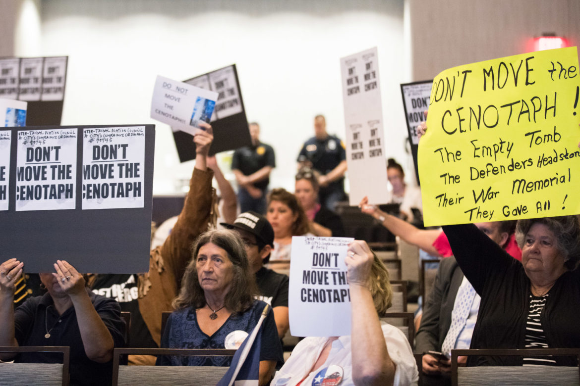 Signs pleading the committee not to remove the cenotaph are held up throughout most of the meeting.