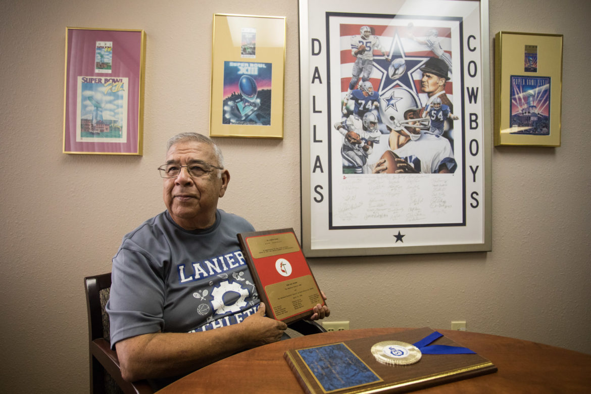 Alex Gonzales sits in his office's conference room with his awards in front of his Dallas Cowboy appreciation wall.