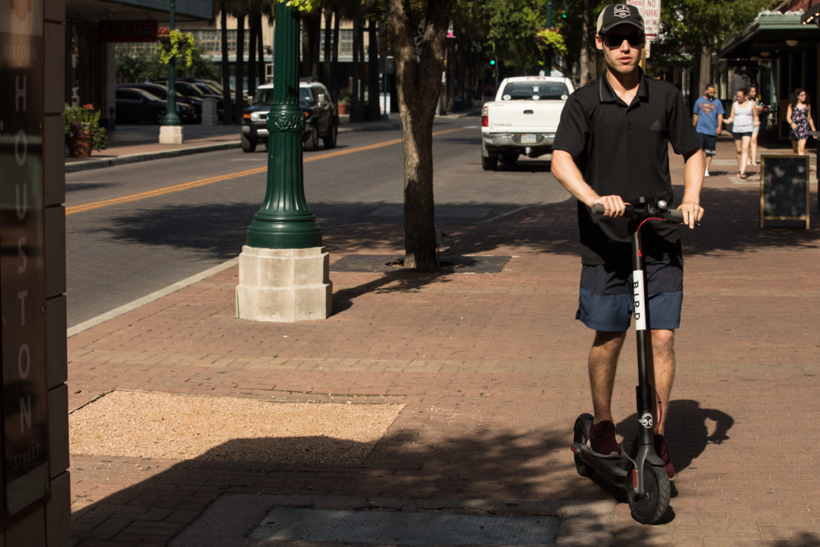 A young man rides a Bird scooter on a sidewalk down East Houston Street.