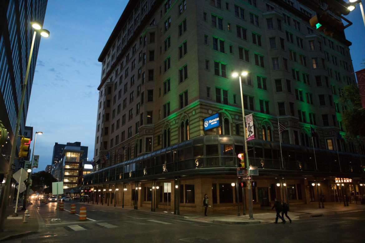 The facade of the Sheraton Gunter hotel is lit with green lights just before dark.