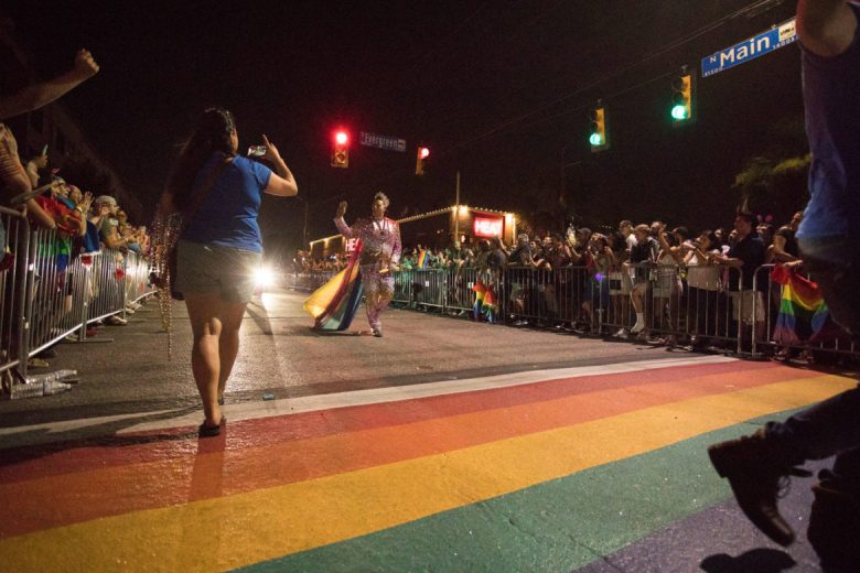 The royalty in the Official Gay Universe Pageant System approach the rainbow crosswalk.