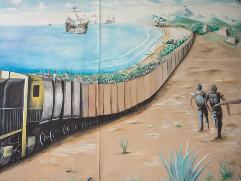 A mural depicting a train is painted on the outside of the RAICES office.