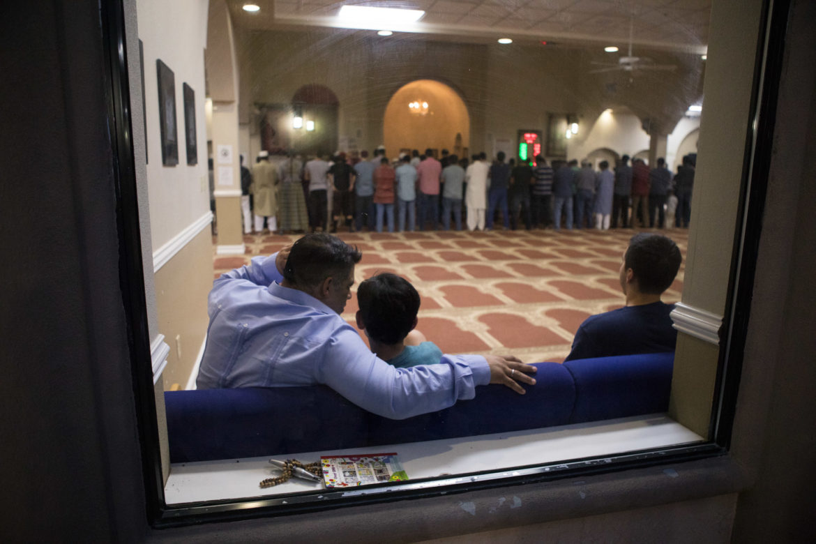 Councilman Manny Peláez (D8) (left) and his son Max watch as the Maghreb prayer takes place.