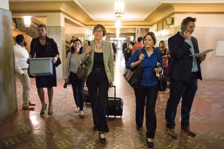 (From left) Amanda Moore, Alejandra Lopez, Martha Owen, and Shelley Potter walk through the hallway in the Bexar County Courthouse to their assigned courtroom.