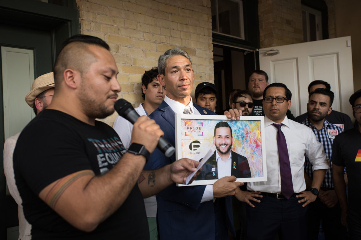 Eric Edward Schell presents an image from his Pride Portraits project to Mayor Ron Nirenberg.