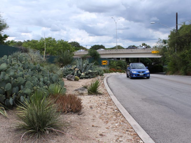 A car rounds a bend on Tuleta Drive, the proposed location of a new parking garage for the San Antonio Zoo and Brackenridge Park.