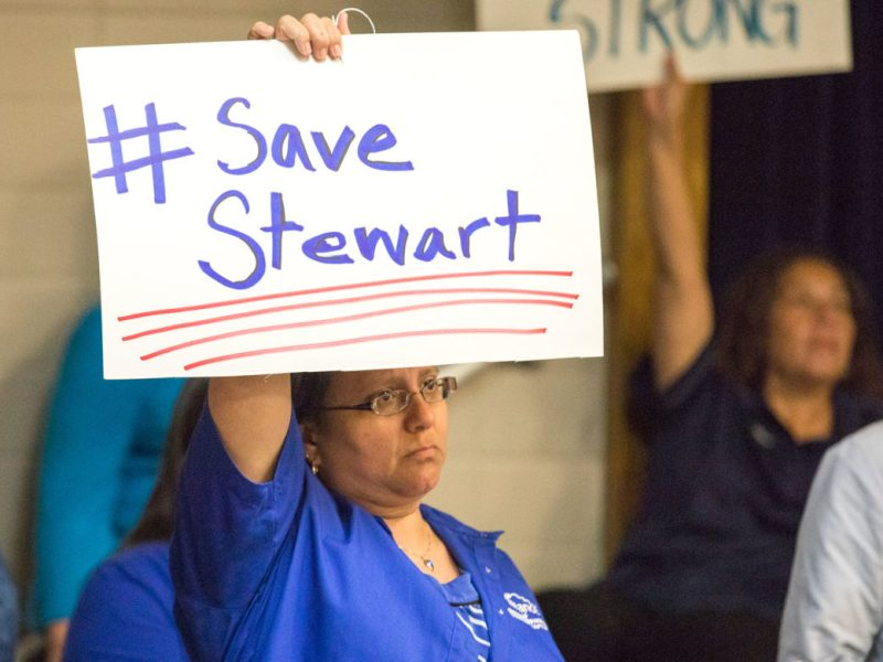 A member of the San Antonio Alliance for of Teachers and Support Personnel holds up a sign in protest of Democracy Prep taking over Stewart Elementary School.