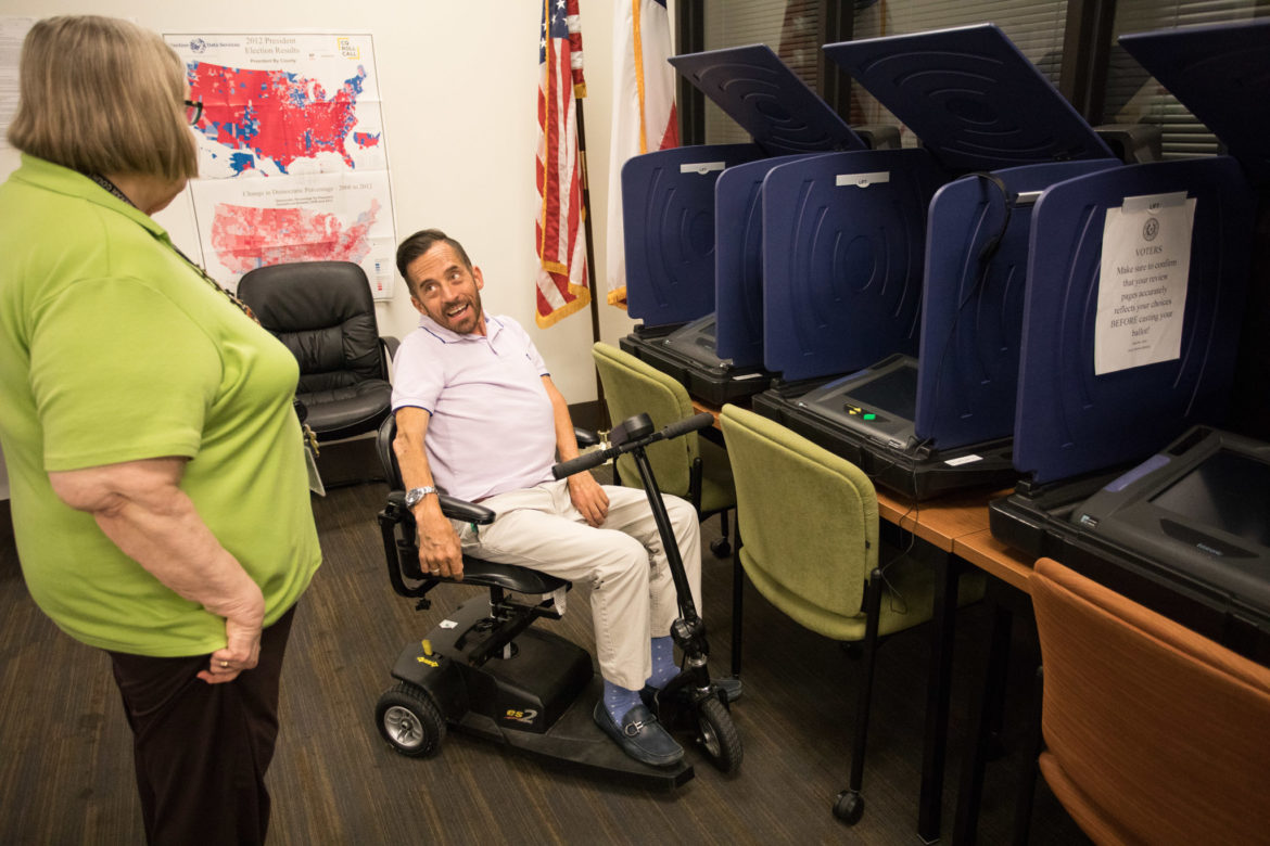 (From left) Jacquelyn Callanen, Bexar County Elections Administrator, shows Adam Flores-Boffa modern-day ballot boxes, which poll workers can carry outside to curbside voters.