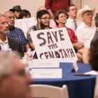 Protesters sit behind tables reserved for the Alamo Citizens Advisory Committee.