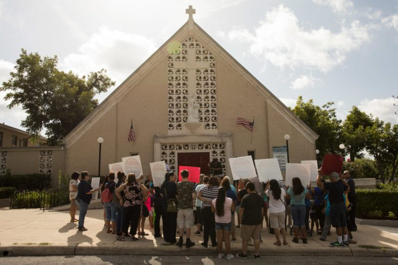 Protesters hold signs outside of St. Anne Catholic Church.