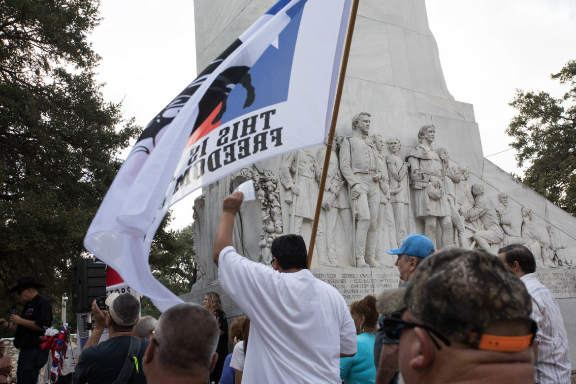 A protester waves a This is Texas Freedom Force flag in front of the Cenotaph in support of not moving the empty tomb.