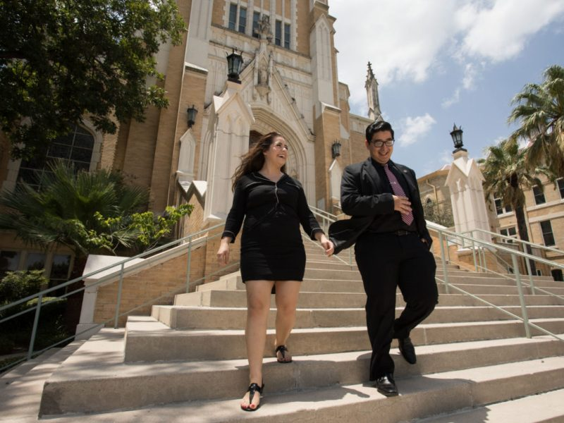 (From left) Our Lady of the Lake University students Gina Vasquez and Enrique Robles walk down the Sacred Heart Chapel steps.