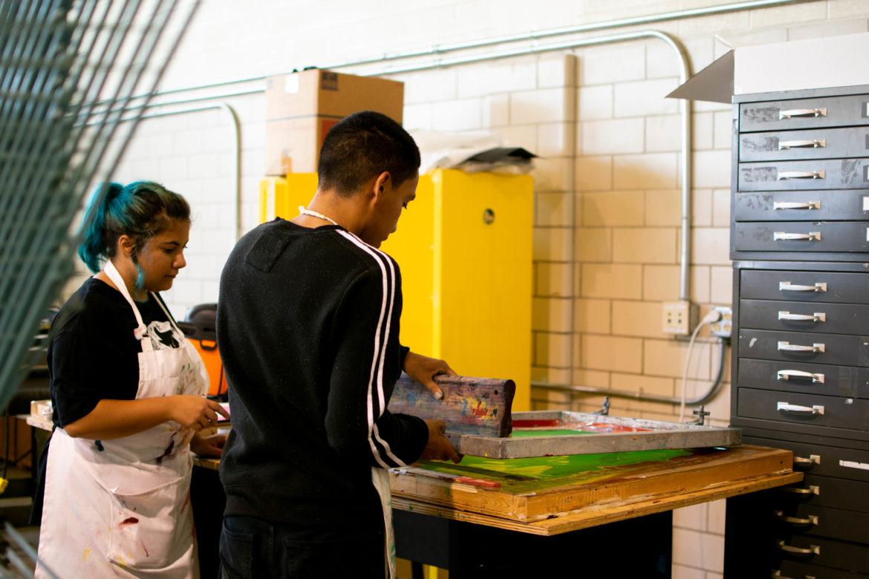Olivia Valenzuela, La Printería apprentice, (left) helps a student use a squeegee to spread ink across the screen.