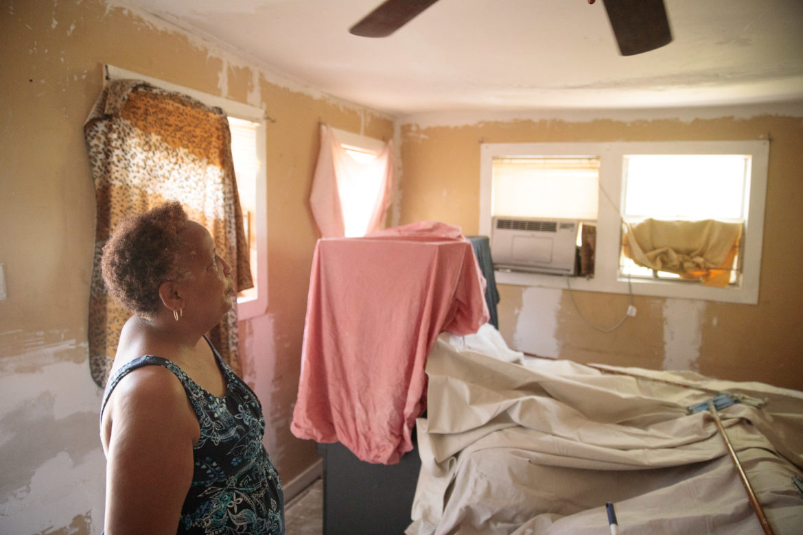 Debra Clay looks up into her living room which is in the middle of being rehabilitated by Blueprint Ministries.