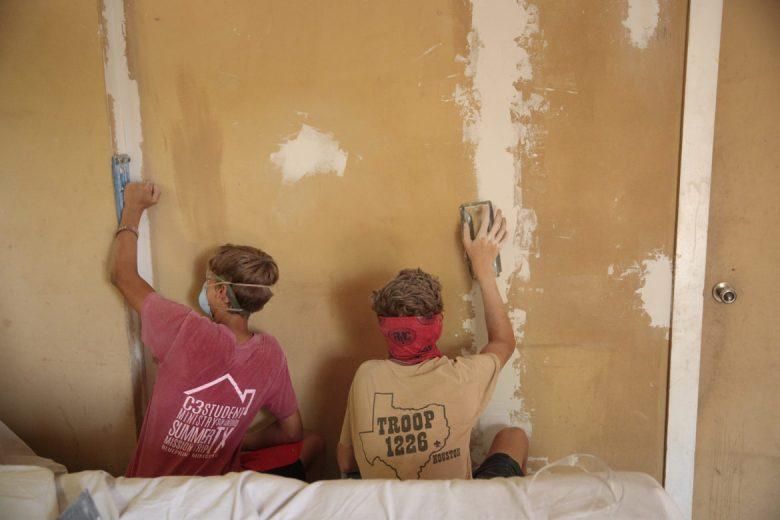 Volunteers from Christ Community Church in Houston Texas sand interior walls at Debra Clay's house.