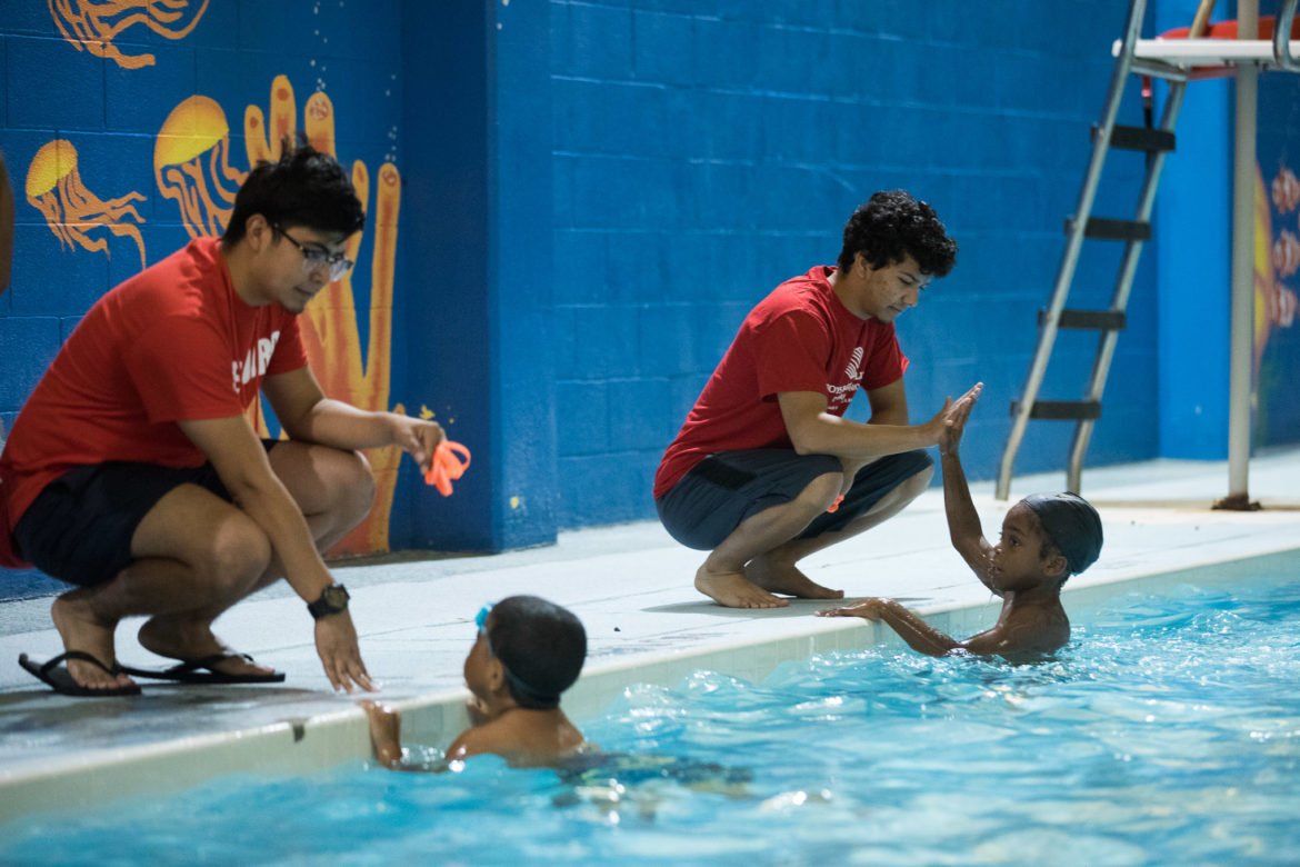 A lifeguard high fives a participant after successfully swimming across the pool.