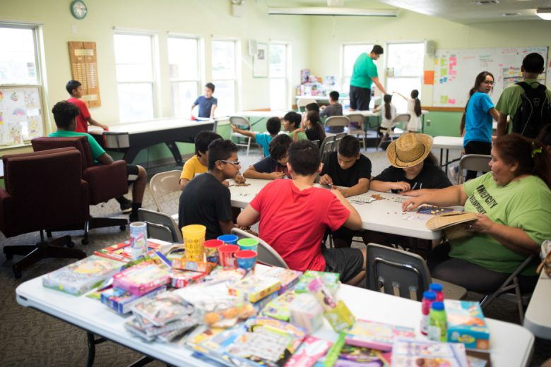 Children and volunteers play bingo, air hockey, board games, and other activities at Inner City Development.