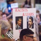 """A sign calling Mayor Ron Nirenberg and Councilman Roberto Treviño (D1) """"racists and liars"""" is held up during the voting."""