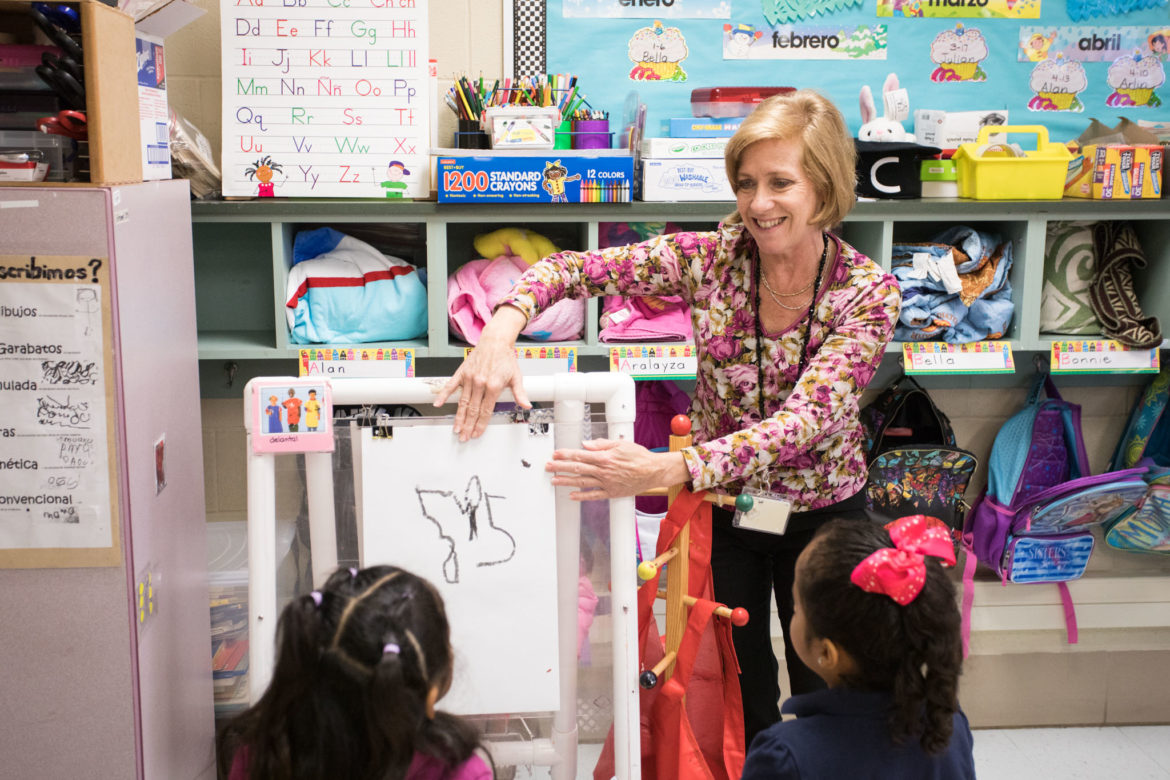 Carvajal Early Childhood Education Center teacher Andrea Greimel shows her students how to properly place the paper on the easel.